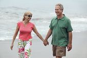 image of early 60s  - Couple Walking Hand in Hand on Beach - JPG