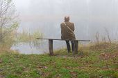 Senior Man Sitting Lonely On A Bench On Riverside On Misty Autumnal Monring poster