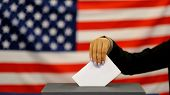 Woman Putting A Ballot In A Ballot Box On Election Day. Close Up Of Hand With White Votes Paper On U poster