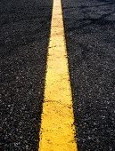 Yellow line on a black paved road
