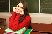 beautiful teen girl high achiever in classroom near desk happy smiling