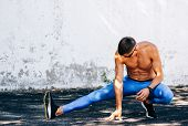 Image Of Jogger Man Stretching Before Exercises Outdoors Against Concrete Wall. Athlete Male Stretch poster