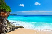 Sandy beach with rocky mountains and clear water of Indian ocean at sunny day. Bali, Indonesia