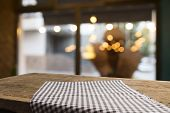 Empty Wood Table Top On Blur Light Gold Bokeh Of Cafe Restaurant In Dark Background poster