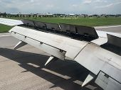 An Airplane Window View Of Wing And Flaps After Landing. Landing Aircraft At The Airport. Braking Of poster