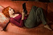 Curly woman on a sofa with ebook