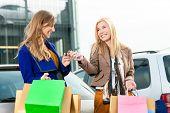 Duas mulheres foram às compras em um shopping ou centro comercial e agora dirigindo para casa com seu carro