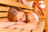 Sauna wellness - young happy women, presumably friends, in Spa, one girl resting on bench in front