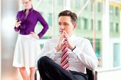 Business people - boss and secretary in office, he is sitting and she makes a phone call