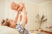 Happy Moment Of Boy Baby And His Mother. Beautiful Mom Rising The Kid In Bedroom. Kids Laughing Happ poster