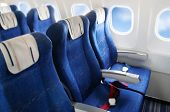 stock photo of aeroplane  - seat rows in a commercial airplane cabin - JPG