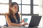 Concentrated Business Woman Is Working On Workplace. Young Asian Female Sitting And Using Laptop Com poster