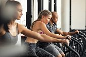 Group of determined multiethnic people at gym exercising on stationary bike. Concentrated fitness wo poster