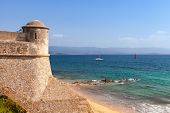 Coastal Landscape Of Corsica Island La Citadelle And Sandy Beach. This Old Coastal Stone Fortress Is poster