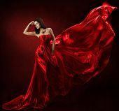 stock photo of provocative  - Woman in red waving dress dancing with flying fabric - JPG