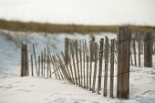 old fence on the sandy beach dunes