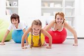Happy people exercising - woman and kids with large gymnastic balls