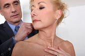 Man attaching necklace to wife's neck