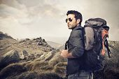 handsome young man with backpack in the mountains