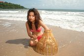 Pretty Asian Woman With Coop-like Trap For Catching Fish In Shallow Water .