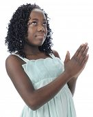 Close-up of a beautiful preteen looking heavenward as she holds her hands in prayer.  On a white bac