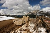 stock photo of colorado high country  - Mountain road with snow fence blue sky and clouds - JPG