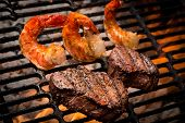 stock photo of flame-grilled  - Big shrimp on a grill with flames