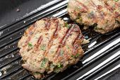 Homemade beefburgers, or beef patties, cooking in a ridged grill-pan