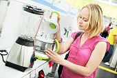 Young woman choosing kitchen mixer blender in home appliance shopping mall supermarket