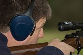 picture of shooting-range  - A close up image of a middle aged man siting in his rifle at the local gun club - JPG