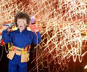 Funny little boy simulating electric shock with many sparks