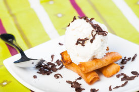 stock photo of lumpia  - fried custard wrapped lumpia wrapper topped with vanilla ice cream and shaved truffle chocolates - JPG