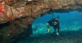 Diver Exploring A Lava Arch In Hawaii