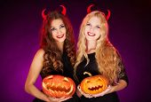 Portrait of two horned females with carved Halloween pumpkins looking at camera