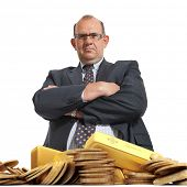 Angry looking man and a pile of gold