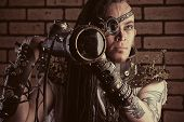 Portrait of a steampunk man with a mechanical devices over brick wall.