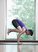 Man with legs off the ground and balancing in yoga position