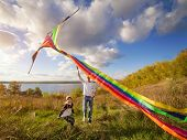 stock photo of kites  - father with son in autumn playing with kite - JPG