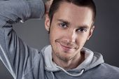 Closeup of young man with hand on head on gray background
