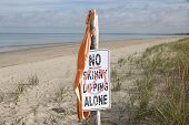 Bathing Suit Hanging From Skinny Dipping Sign At Beach