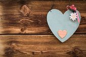 wooden grey heart with edelweiss on sun burned wood