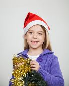 Portrait of smiling girl wearing Santa hat holding tinsels at home during Christmas