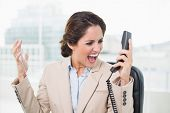 Outraged businesswoman shouting at phone in bright office