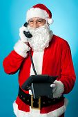 Modern Santa Passing Greetings Over A Phone Call