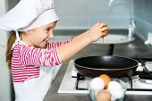 happy little girl cracking an egg over pan
