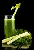 Glass of green vegetable juice and celery isolated on black