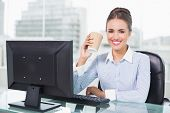 Happy brunette businesswoman holding disposable cup in bright office