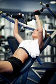 picture of muscle builder  - Smiling athletic woman pumping up muscles in a gym - JPG