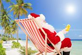 Santa Claus lying on a beach chair and drinking orange cocktail, enjoying on a sunny day, on a beach