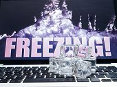 Ice cubes on computer keyboard with Ice on background FREEZING
